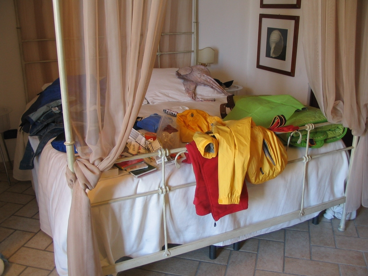 An array of colorful clothes scattered on a bed.