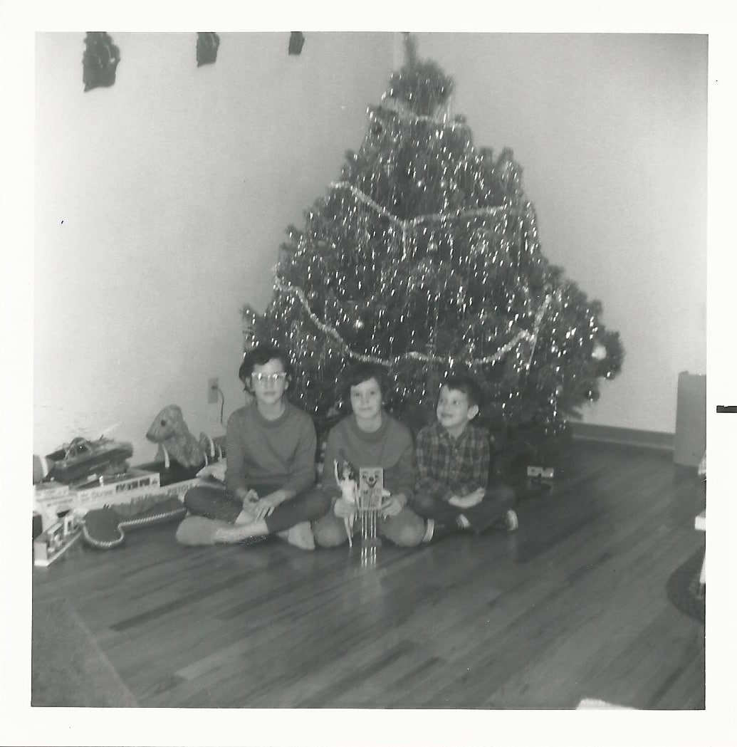 Black & white picture of 3 kids at Christmas tree in 1965