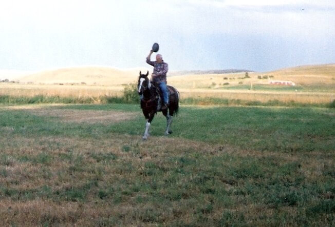 Dad riding a horse, waving his hat