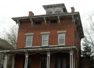 brick home requiring work with damaged cupola